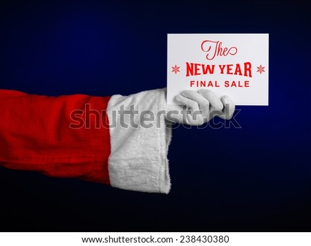 Christmas and New Year discounts topic: Hand of Santa Claus holding a white card with a Christmas discount on an isolated dark blue background - stock photo