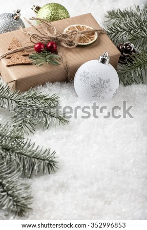 Christmas and New Year gift box with Christmas decorations on the snow