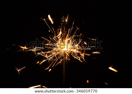 Christmas and New Year party sparkler on black - stock photo
