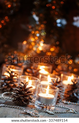 Christmas and New Year's background with candles, fir cones and beads on an old wooden table in rustic style, toned image, selective focus - stock photo