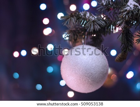 Christmas and New Year`s bokeh image. White ball toy decorations on tree, fir cones and tree branches.  Greeting card blue Background concept with holiday tinsel with copyspace place for text or logo.
