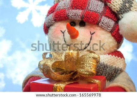 Christmas and New Year snowman snowman with gift on snow background - stock photo