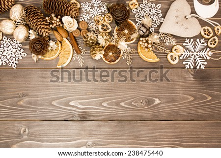 Christmas and new year winter cozy border with dry spices, fir cones and other decor on a dark wooden background.