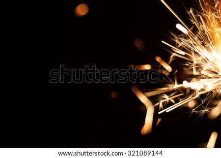 Christmas and newyear party sparkler on black background with space for text - stock photo