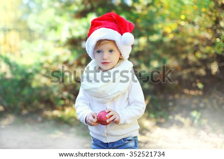 Christmas and people concept - child in santa red hat with ball
