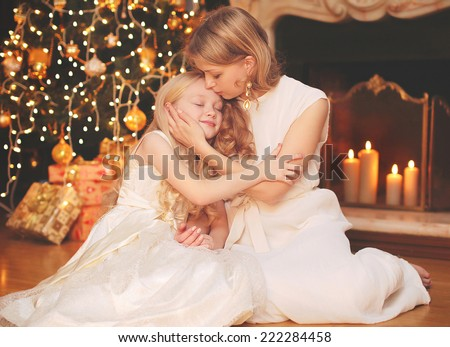 Christmas and people concept - happy mother and child near christmas tree and fireplace - stock photo