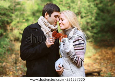 Christmas and people concept - happy pretty young couple in love outdoors against christmas tree in winter day - stock photo