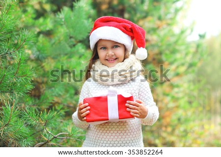 Christmas and people concept - happy smiling child in santa red hat with box gift - stock photo