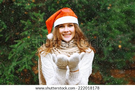 Christmas and people concept - happy young girl in winter hat near tree having fun outdoors - stock photo