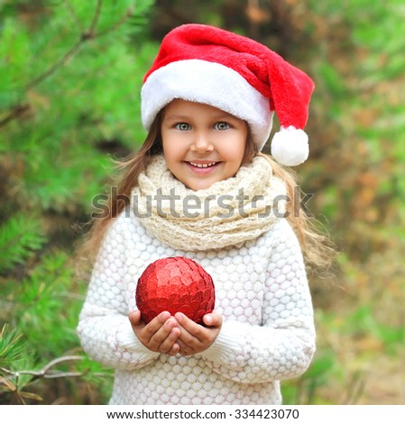 Christmas and people concept - little smiling girl child in santa red hat with ball - stock photo