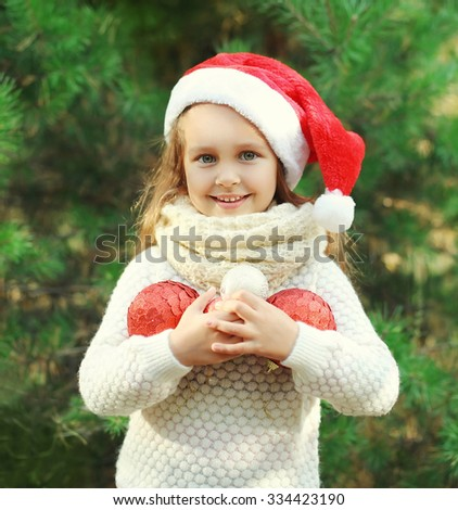 Christmas and people concept - little smiling girl child in santa red hat with balls - stock photo