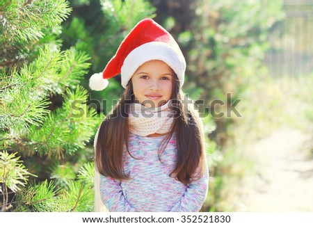 Christmas and people concept - portrait little girl child in santa red hat - stock photo