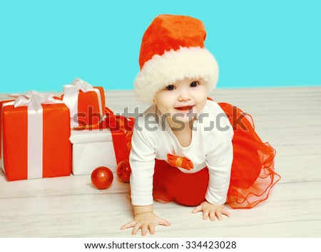 Christmas and people concept - smiling child in santa red hat with boxes gifts crawls on floor - stock photo
