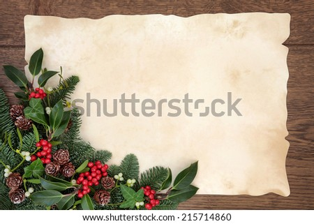 Christmas and winter background border with fir, holly, ivy, mistletoe and pine cones over old parchment paper and oak wood. - stock photo