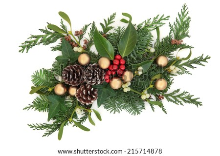Christmas and winter decoration with holly, gold baubles, mistletoe, fir and cedar leaf sprigs with pine cones over white background. - stock photo