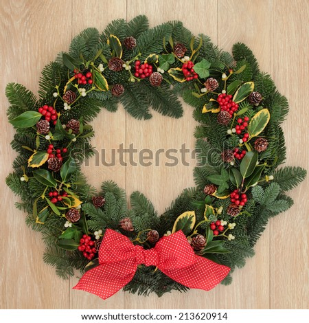 Christmas and winter wreath with red bow, holly, ivy, mistletoe, spruce fir and pine cones over oak background.