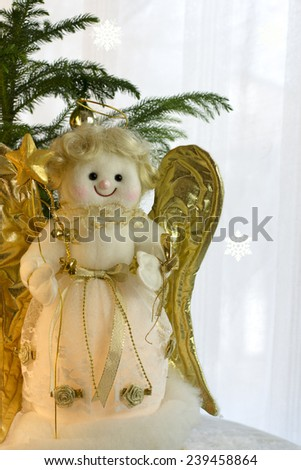 Christmas angel toy with the gold wings  on a white background. Christmas angel decoration - stock photo