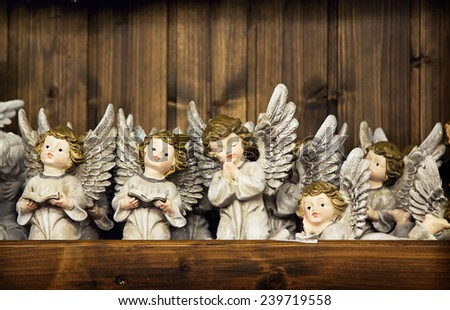 Christmas angels toy with the sparked wings on a wooden wall background. Christmas angel decoration  - stock photo