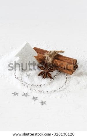 Christmas arrangement, cinnamon sticks and white decoration - stock photo