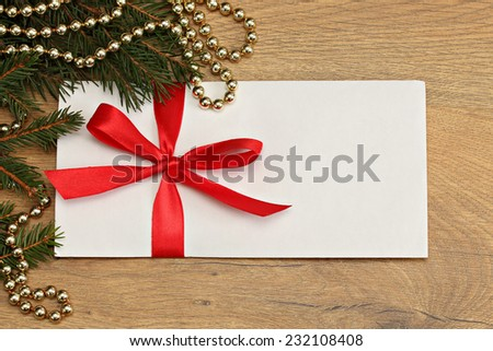 Christmas arrangement of the branches of trees, an envelope with a red bow and a garland of gold beads