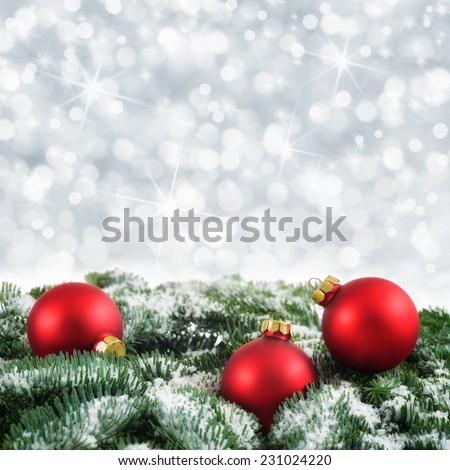 Christmas arrangement with red baubles on snow-covered fir twigs and a silver background of out-of-focus lights - stock photo