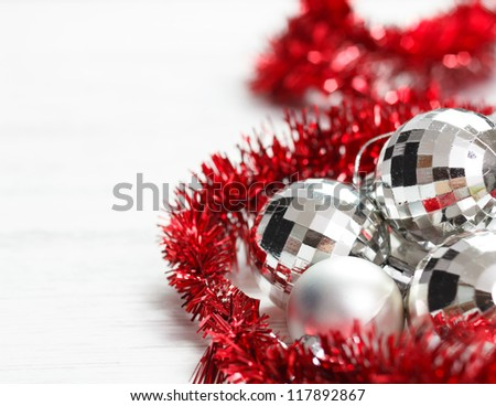 Christmas arrangement with silver baubles and red garland.Copy space on left.