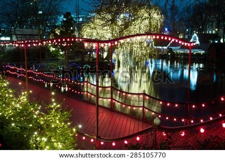 Christmas at the Tivoli in Copenhagen at night. Illuminations on the lake - stock photo