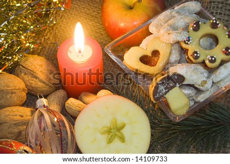 Christmas atmosphere - candle, apple, sweets and Christmas decorations - stock photo