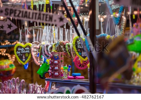 Christmas atmosphere of the city at night. Christmas sweets. Gingerbread-bears. Gingerbread-heart. Caramel rolls. Christmas Fair at night. Germany. Europe