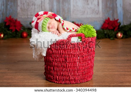 Christmas Baby.  Adorable newborn fast asleep in a red basket and wearing a long read and white striped hat.  Christmas decor in the background.  Room for your text.