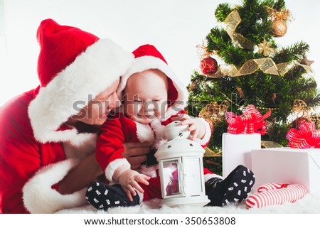 Christmas baby and mom under the fir tree isolated - stock photo