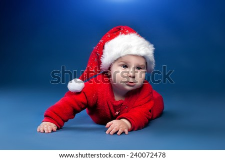 Christmas baby boy in Santa's hat is lying on blue plaid - stock photo