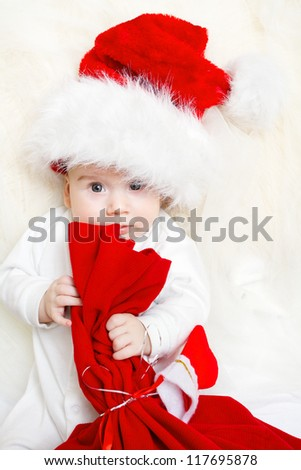 Christmas baby holding red bag in Santa Claus hat - stock photo