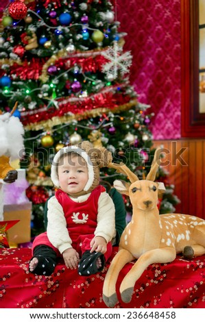 Christmas baby in hat near gift box and new year fir tree - stock photo