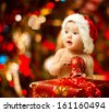 Christmas Baby in Santa Hat, Child holding Red Ball near Present Gift Box over Holiday Lights background - stock photo