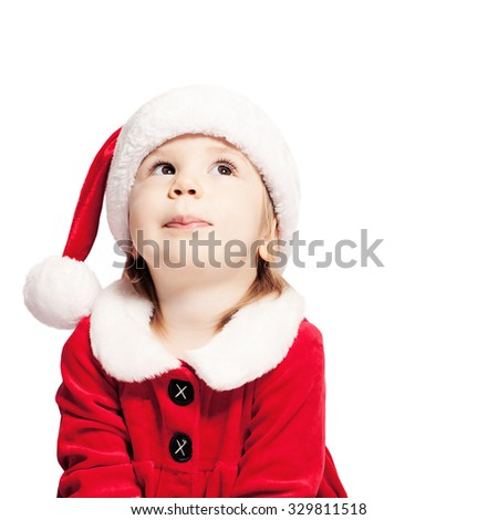 Christmas Baby in Santa Hat Looking Up. Child Isolated on White - stock photo