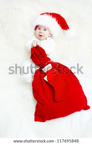 Christmas baby wearing Santa Claus hat holding red gift bag with sock - stock photo