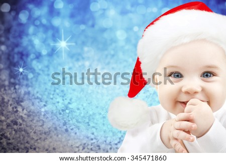 christmas, babyhood, childhood and people concept - happy baby in santa hat over blue glitter holidays lights background - stock photo