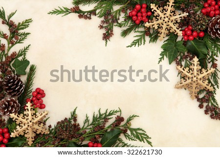 Christmas background border with gold snowflake bauble decorations, holly, ivy and winter greenery over old parchment paper. - stock photo