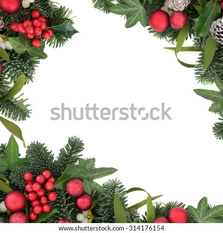 Christmas background border with holly, red bauble decorations, ivy, mistletoe, snow covered pine cones and blue spruce fir over white. - stock photo