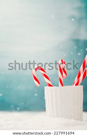 Christmas background. Candy canes on snow, Xmas decoration - stock photo