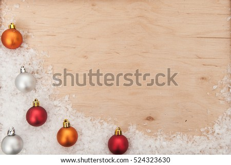 Christmas background. Christmas balls, snowflakes and snow on a wooden background