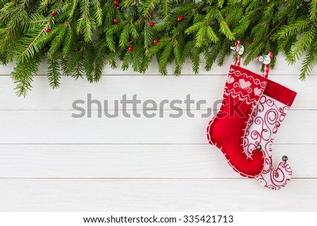 Christmas background. Christmas fir tree, red Christmas socks on white wooden board background with copy space.