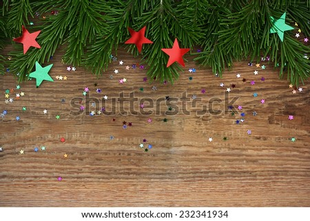 Christmas background: fir-tree branches with multi-colored confetti on old wooden background - stock photo