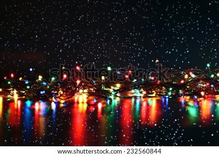 Christmas background, garland lights toys snowflakes snow glare night - stock photo