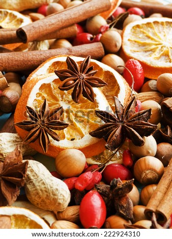 Christmas background made of nuts, dried oranges, and spices. Shallow dof. - stock photo