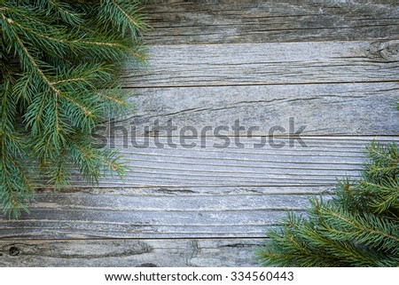 Christmas background of fir tree branches on an old rustic wooden board, copy space for text, top view.