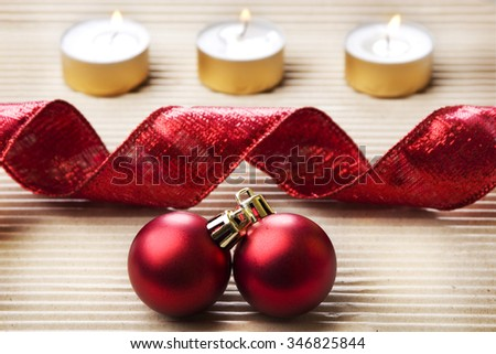 Christmas background on textured grey paper with burning candles, ribbon and baubles - stock photo