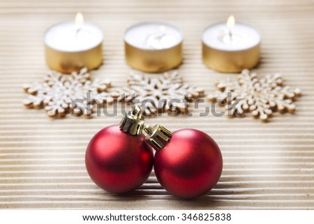 Christmas background on textured grey paper with burning candles, snowflakes and baubles - stock photo