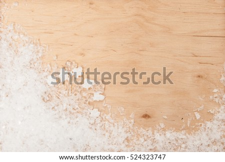 Christmas background. Snow and snowflakes on a wooden background